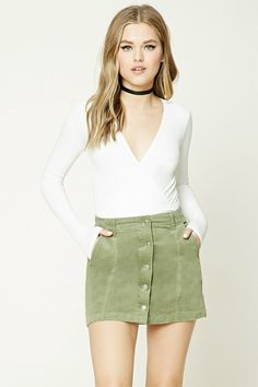 A corduroy mini skirt featuring a button front, belt loops, and front slant pockets.