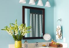 Accessories are a renter's best friend. Add a patterned shower curtain and complementary decor to brighten a bathroom.