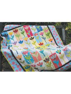 """Tessie Quilt Pattern $9. This bright, scrappy posy pattern is sure to brighten any little girl's room. A great stash buster! Pretty flowers grace this sweet quilt that can be machine or hand appliqued. She will love to cozy up to this colorful design. Pattern includes instructions for a mini quilt as well. Finished sizes are 52 1/2"""" x 63 1/2"""" and 28"""" x 35 3/4"""". Skill Level: Beginner."""