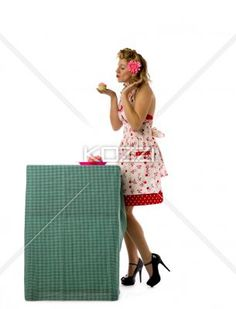 side view of a woman about to kiss a cupcake. - Side view of a woman about to kiss a cupcake while standing over white background, Model: Carrie Galbraith