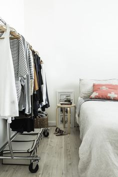 Open clothes rail, cross cushion in the bedroom of a pared-back Australian home in neutrals. Photographer: Maree Homer.