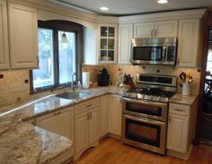 This kitchen remodel shows Dura Supreme cabinets in antique white, with a glaze.