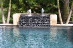 Keep your #swimmingpool circulated with a beautiful #waterfall feature designed by the experts at Swimming Pools By Ike Jr.