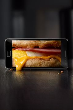 """Photo retouching for Leo Burnett's Arc Worldwide to introduce McDonald's new mobile app. The brief was for the food photography to appear as a screen image, yet have portions of the food """"come out"""" of phone, touching the countertop. Reflections, shadows, condensation and other details were added to enhance the illusion. Explore more Filtre Studio Chicago advertising retouching and Photoshop wizardry at filtrestudio.com"""