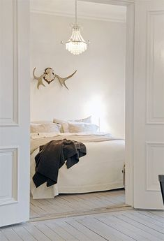 light cream walls, heavy molding on tall doors, crystal chandelier over white linen, multi-textured bed, charcoal throw, antler mount over bed - interesting & calm at the same time
