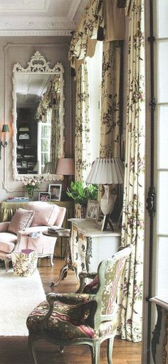 Nicky Haslam: This room totally seduces.  First of all, it simply has good bones -- Tall windows, high ceiling. Decorating style ramps up the old-world romantic feel: tall vintage mirror painted whitie, soft old-fashioned print fabric with off-white background, color scheme in faded pinks, greens and more soft whites ...