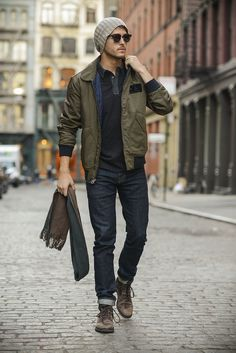 Shop this look on Lookastic: https://lookastic.com/men/looks/bomber-jacket-polo-jeans-boots-beanie-scarf-sunglasses/13365 — Grey Beanie — Dark Brown Sunglasses — Charcoal Polo — Olive Bomber Jacket — Dark Brown Herringbone Scarf — Navy Jeans — Dark Brown Leather Boots