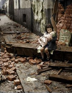 Girl with her doll after a bombing raid in WWII London.
