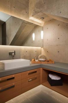 This bathroom features back-lit lighting and concrete walls