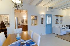 TRAMOUNTANA VILLA, SANTORINI. As you enter you reach a large open-plan social area that includes the living room and the dining room. It's furnished with comfy sofas. It also has a large window with views of the sea.