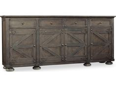Influenced by antique style, this storage credenza features four doors with a barn-like design. Adjustable shelving behind each door creates a custom appeal to the piece and allows you to fit items of different sizes with ease. Four drawers, including a single drop-front drawer, are perfect for organizing silverware and napkins when you're not using them. Plug a slow cooker or warming plate into the outlet of this credenza to keep your food warm between servings.