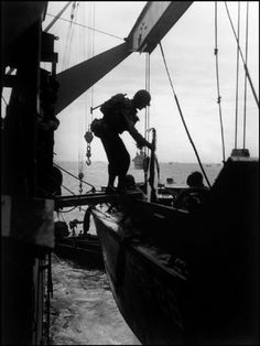 FRANCE—Off the coast of Normandy, American troops transfer from troop ships to landing crafts before assaulting Omaha Beach, June 6, 1944. © Robert Capa © International Center of Photography / Magnum Photos
