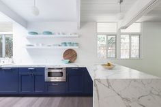 Carrara marble constrasts with the blue-painted cabinetry.