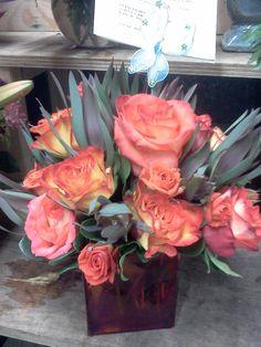 Que hermosas Rosas color naranja en un cubo como vase del mismo color. Un estilo compacto y muy elegante. Se vera perfecto en su escritorio, mesa de noche o mejor a un en la sala de su casa!!