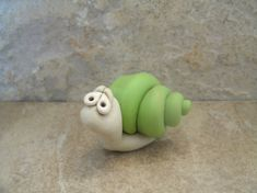 A whimsical garden snail created from polymer clay. This is an original design that stands just over an inch tall and is approximately 2