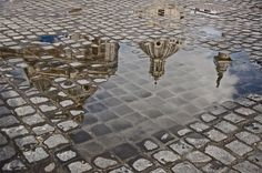 """Near the Vatican, Churches' rooftops and the heavens above reflect in the pavements's puddles.""Rome, Italy 