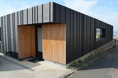 Varied size board and batten with vertical wood siding House Cladding, Metal Cladding, Exterior Cladding, Metal Facade, Metal Buildings, Building Exterior, Building Design, Building Ideas, Facade Design