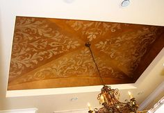 The groin ceiling was layered with Modern Masters bronze and gold tones, which were woven into each other to create a smooth, rich finish.  The four corner stencil designs are by Modello™ Designs. Artists: Ashlie Bickford and Kindra Benge.
