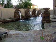 Autumn blend flagstone surrounds this resort style pool featuring natural stone columns, copper scuppers and fire bowls in Phoenix, AZ. - www.lonestaraz.com
