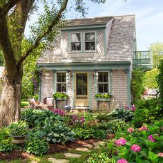 Cedar shingles cured by the salt air, window brackets borrowed from the 1880s main house, a sunny balcony, and a shady elm give the former garage a storybook look.The entry lights and cast-iron front step are salvaged finds.