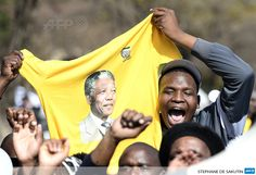 SOUTH AFRICA, Pretoria : People celebrate the birthday of former South African President Nelson Mandela on July 18, 2013 outside the Medi Clinic Heart Hospital in Pretoria.AFP PHOTO / STEPHANE DE SAKUTIN