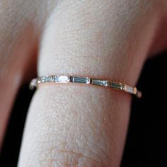 "Nora Kogan: The ""Skinny"" ring in 18k rose gold, set with G color, VVS1 quality, diamond baguettes. Measuring 1.3mm wide, it's our most delicate hand-made band. Total diamond weight is .46ct. Also available in 18k white and yellow gold."