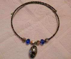 This memory wire necklace is made with seed beads and accented with a glass pendant as shown in pictures. It will fit a 16 to 19 neck. It is a