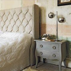 Cabecero tapizado en color piedra con mesilla pintada en gris. Lámpara estilo vintage en cromo