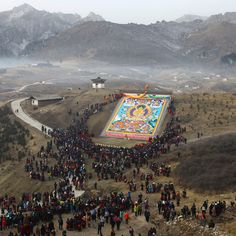 Tibetan Buddhists and tourists view a giant Thangka, a religious silk embroidery or painting unique to Tibet, displayed on a hill near the Langmu Temple in Gannan Tibetan Autonomous Prefecture
