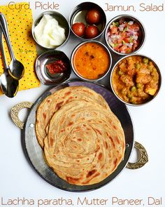 Indian food - mutter paneer, lachha paratha, dal fry, gulab jamun, dahi, pickle.
