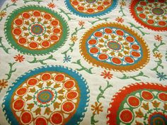 Suzani - A pattern, often embroidered, of disk shaped motifs decorated as suns, moons, or flowers, in a style originating from Central Asia. See also, Medallion - Fabric Glossary