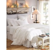 Love the all white bedding and shelf w candles over it
