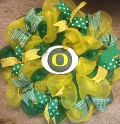 Poly Deco Mesh wreath for the University of Oregon Ducks in colors of green & yellow. Accented with ribbons in the green & yellow team colors as well as ribbon looking like football field yardage.