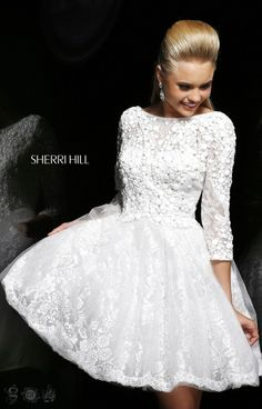 Sherri Hill 4303 is a darling short dress ideal for receptions, parties, prom and more! This gown has a trendy high neckline and 3/4 length sleeves with a deep V in the back. The upper bodice is detailed with sheer lace and geometric stones that make the perfect glamorous look! The full mini skirt is the finishing touch to make this style unique and one of a kind!