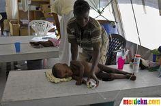 Seorang anak yang tengah dehidrasi karena kolera dibantu ibunya di sebuah pusat pengobatan kolera yang dijalankan dokter sukarelawan Medecins Sans Frontieres (MSF) di Port-au-Prince.
