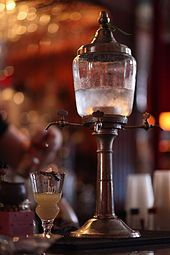 In 19th century Parisian cafés, upon receiving an order for an absinthe, a waiter would present the patron with a dose of absinthe in a suitable glass, sugar, absinthe spoon, and a carafe of iced water.[63] It was up to the patron to prepare the drink, as the inclusion or omission of sugar was strictly an individual preference, as was the amount of water used. As the popularity of the drink increased, additional accoutrements of preparation appeared, including the absinthe fountain, which…