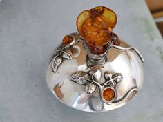 Beautiful vintage find handmade sterling silver perfume bottle with carved amber flower and cabs decorated on top. Its in great vintage condition. Bottle is not marked and acid tested positive for sterling silver or higher. Measurement: Perfume bottle weights 44.5 grams, measures 2.3 inch
