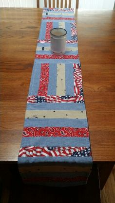 """Table runner made jelly roll style. I cut the fabric in 2 1/2"""" strips. Then I sewed each long strip together in the 6 row pattern sequence. I then cut into 11 3/4"""" squares and sewed them together - switching between horizontal and vertical. I put the jelly roll side of the runner right side against denim fabric the same size. Sewed together leaving opening for turning. Turned, ironed, top stitched opening and then sewed a border around entire runner for decorative effect and to hold front…"""