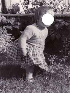 """""""I'd love to know what you think of this photo. It was taken, by my uncle, many years ago in Highfield, Southampton, where we used to live. That's me in the foreground but in the background, close to the shrub, you'll see a face peering over the wall."""