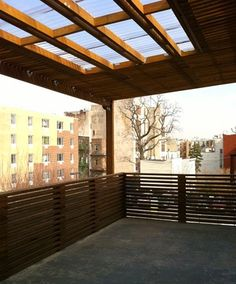 Covered cement patio with horizontal railing, corrugated roof and skylights