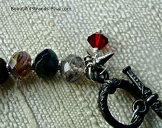 Heroes and Villains Multicolored Glass Bead Bracelet with Red Crystal Charm by BeautifulStrands on Etsy
