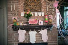 classic pink and green baby shower clothesline on fireplace