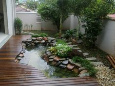 Deck in zen garden has pond cut into it.