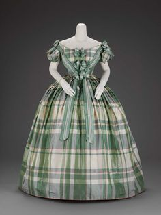 American; about 1859–60  An evening dress in two parts and a pair of matching hair bows (match trimming): taffeta woven with plaid of green, white, and pink...