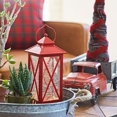 Red lantern and tabletop Christmas tree on coffee table.
