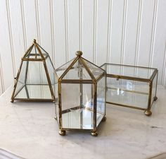 Beautiful glass & brass faceted footed keepsake box. Trapezoid shape with mirror on bottom & hook in center top. Sits on 4 brass ball feet with front brass closure. In very good vintage condition! Hang your favorite ornament, bell or use for holding small figurines! Great for holiday