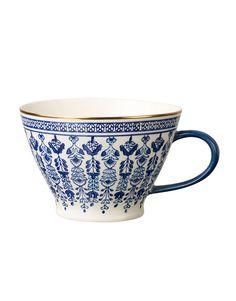 Kopp med guldkant och öra med ett dekorativt mönster