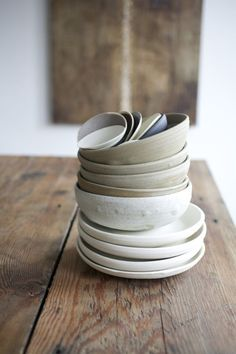 neutral dishes stacked on wooden table