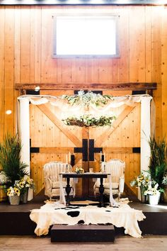 This barn made a lovely setting for an elegant country wedding. Two creamy white pillars, fabric and floral made a dreamy arch over the antique sweetheart table. Chandelier and authentic cowhide rug added some magic. . Event styling, set up, and rentals by On The Side Events & Service.  . Photo by Kelcie Jean Photography.