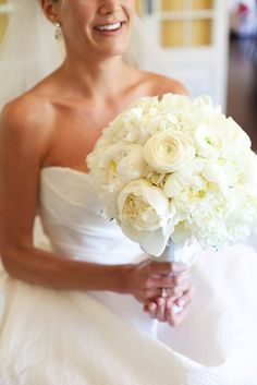 The bride will carry a round clutch bouquet of white hydrangea, ivory peonies, ivory roses, and white ranunculus wrapped in ivory ribbon tied in a bow